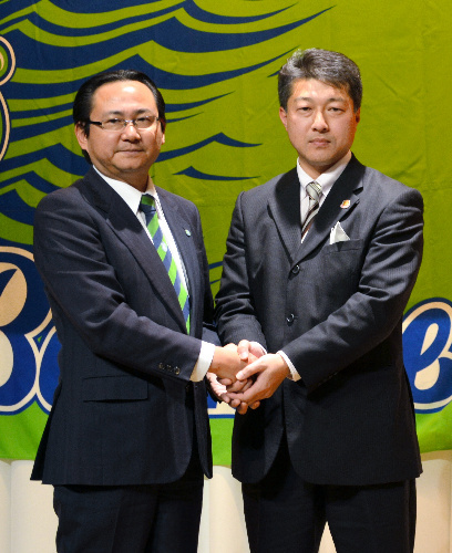 握手を交わす湘南の真壁潔社長(左)と福島の鈴木社長