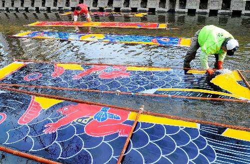 写真:こいのぼりについているノリを洗い流す「のんぼり洗い」=愛知県岩倉市の五条川