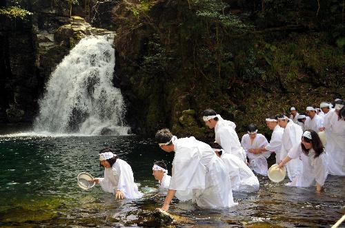 写真:滝つぼに入る白装束の人たち=名張市の赤目四十八滝・千手滝 滝つぼに入る白装束の人たち=名張
