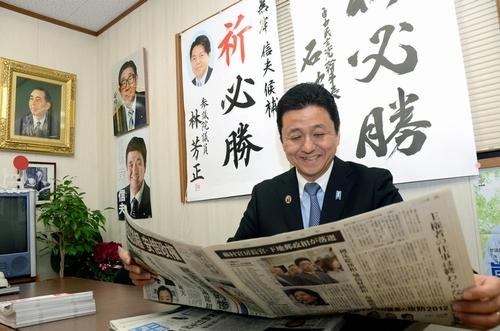 写真:岸信介元首相の遺影(左上)などがかかった事務所で新聞を読む岸信夫氏... 岸信介元首相の遺