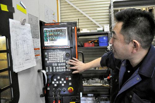 写真:機械のボタンを押すと、加工が始まる