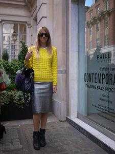鮮やかなイエローのニットの彼女。シルバーのタイトスカートと合わせてシックに。マーガレットハウエルのショー会場で。