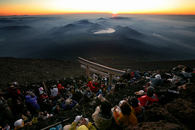 写真 山頂でご来光を眺める登山者たち