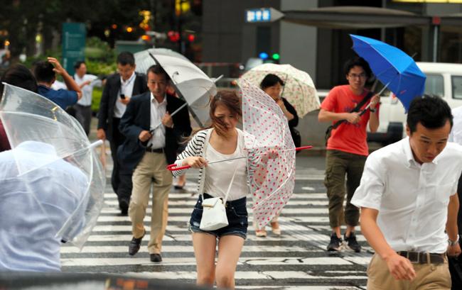 台風による強風の中、駅に向かう...