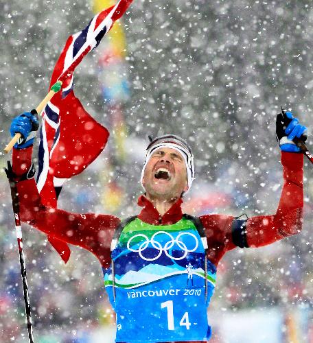写真:バイアスロン男子30キロリレーで、国旗を掲げ首位でゴールするノルウェーの最終走者ビョルンダーレン=AP
