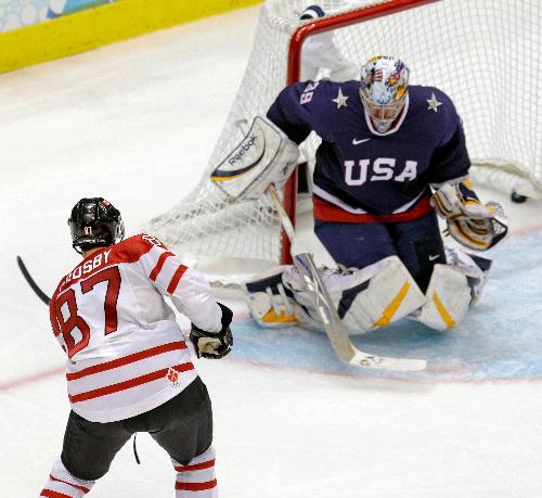 写真: アイスホッケー男子決勝の延長戦でゴールを決めるカナダのクロスビー。米国GKミラー=AP