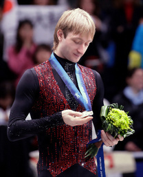 写真: バンクーバーで2月18日、冬季五輪男子フィギュアスケートの表彰式で銀メダルを見つめるロシアのプルシェンコ選手=AP