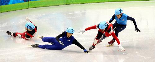 写真: 男子500メートル決勝の最終コーナーで転倒するトランブレ(左端=カナダ)と成始柏(韓国)。バランスを崩しながらもアメリン(カナダ)がトップでゴールし、オーノ(右端=米)は失格となった=飯塚晋一撮影