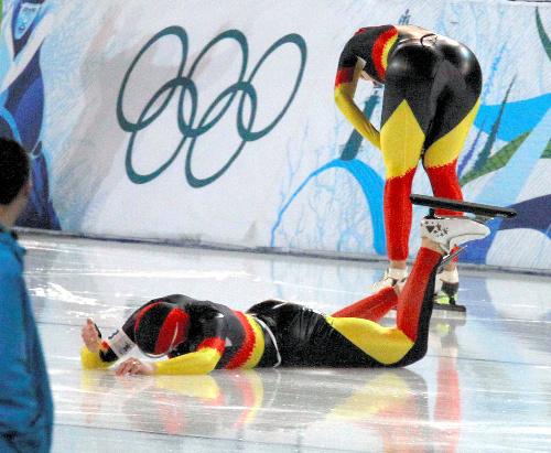 写真:女子団体追い抜き準決勝、転倒しながらゴールしたドイツのフリージンガー(手前)は、負けたと思い右手を氷にたたきつけるが……