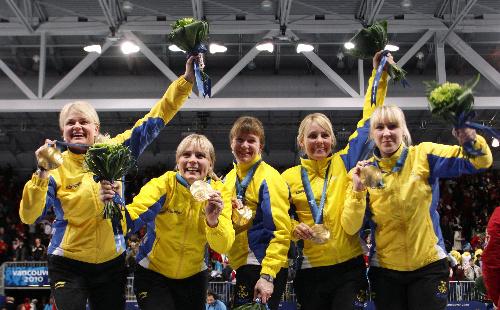 写真: カーリング女子で優勝し、金メダルを手に笑顔のスウェーデンの(左から)ノルベリ、ルンド、リンダール、レモイネ、ベリストローム=ロイター