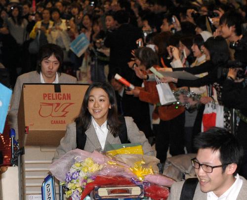 写真: 成田空港で出迎えを受ける(手前から)加藤条治、浅田真央、長島圭一郎=福留庸友撮影