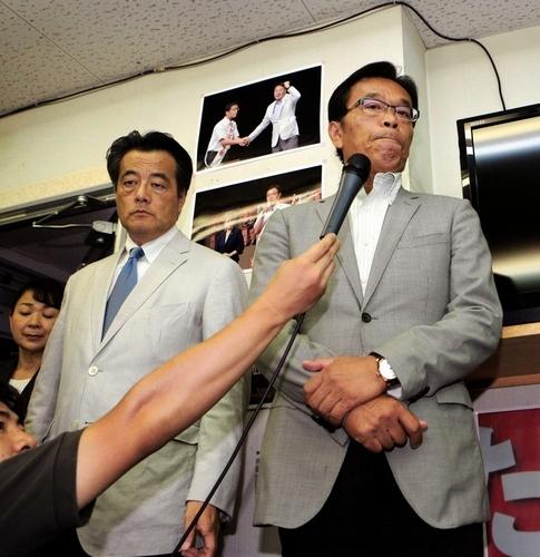 写真:落選が決まり、インタビューに答える民主党の高橋千秋氏(右)。隣に岡... 落選が決まり、イ