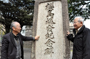 記念碑の前に立つ岩松暉さん(右)と橋村健一さん。「こんなにたくさん見つかると思わなかった」=鹿児島市