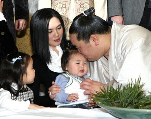 写真 祝賀会で長男のジャミアンドルジくんにキスをする朝青龍。隣は妻のゴンブトゥレン・タミルさんと