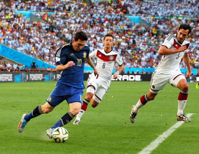前半、ドリブルするアルゼンチンのメッシ(10)をマークするドイツのフンメルス(5)とエジル(8)=上田潤撮影