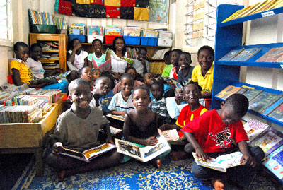 Children spend quality time with their favorite books at their community library-which used to be a container-in Accra. Local director, Joanna Felih, is in the back row, center.