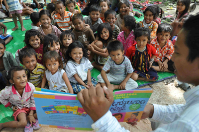 Vuthy Vibolraoth, right, reads a storybook written in Khmer in a village near Phnom Penh.